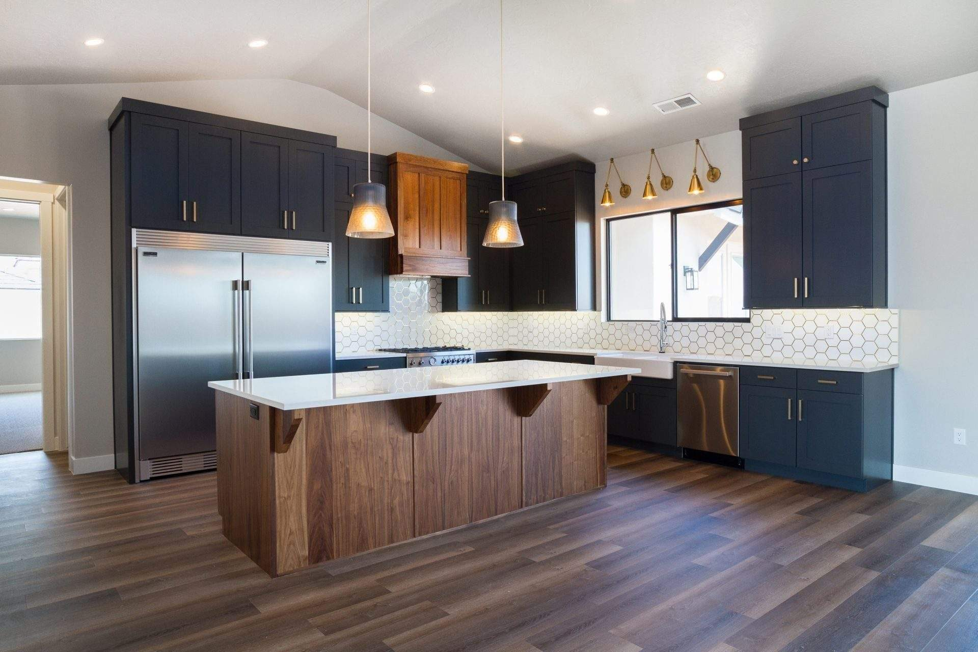 Etch Design Group - custom home with deep gray cabinets and brass accents.