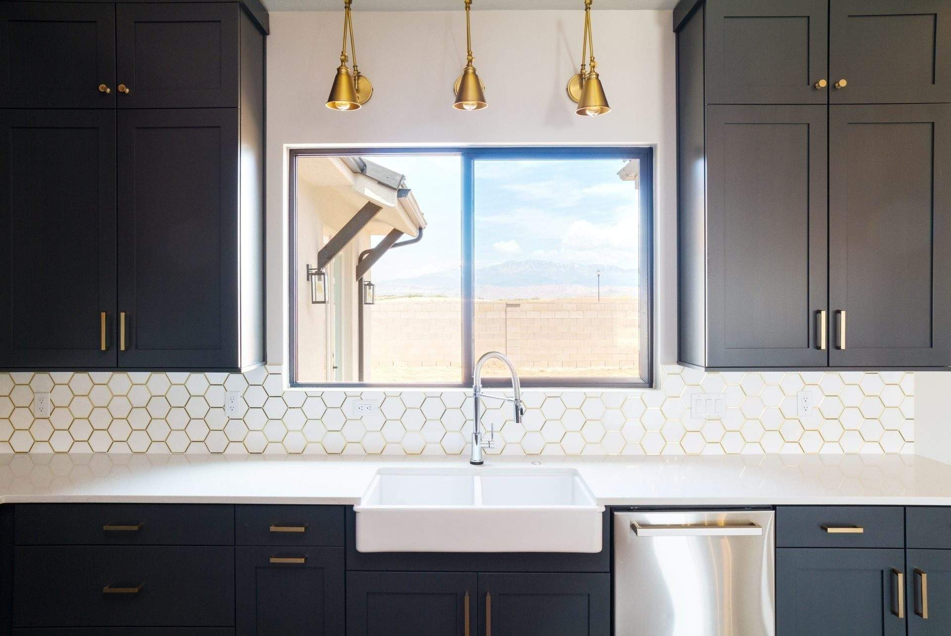 Etch Design Group | custom home with deep gray cabinets and brass accents window over sink | Austin, texas