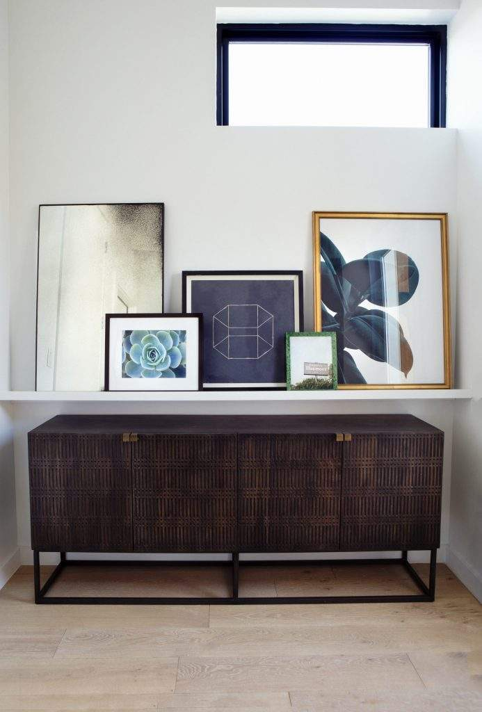 travis heights | dark cabinet with shelf and art above | austin, texas