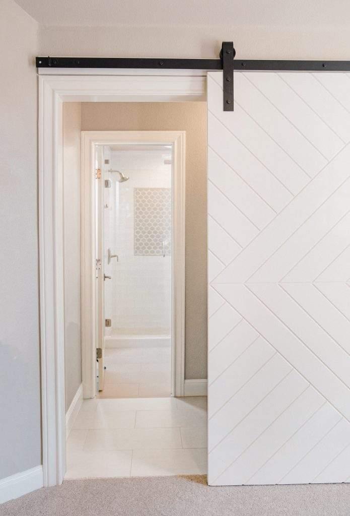 Northwest Balcones - interior design austin | farmhouse door with geometric design looking into bathroom| austin, texas