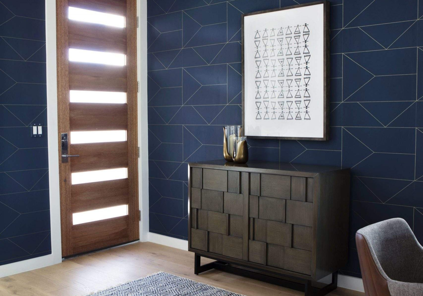 travis heights   cabinet and art work with blue geometric wallpaper near front door 1   austin, texas