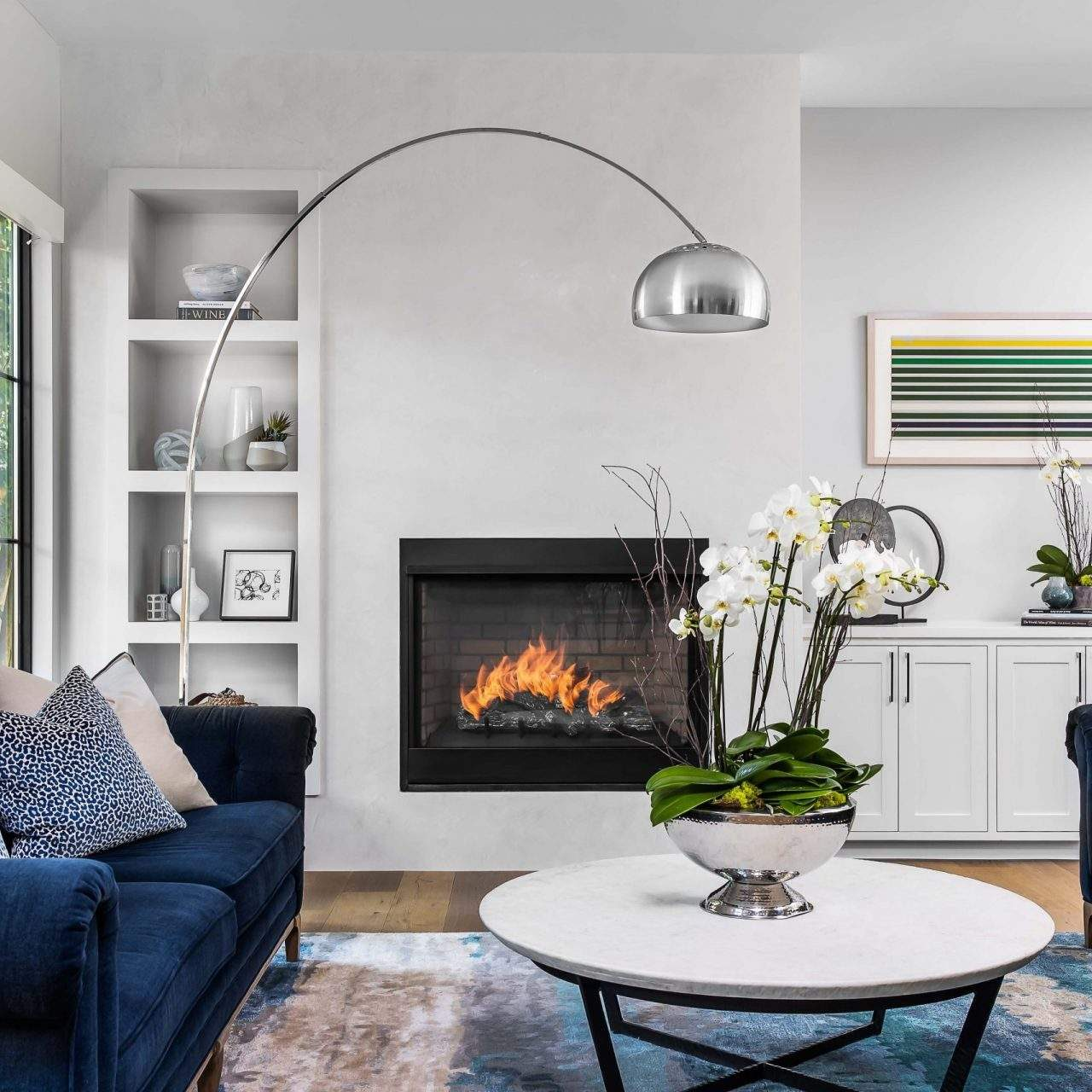 Interior Design, Blue Sofas, fireplace, and large silver floor lamp